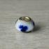 Perle de verre blanche et accents bleus.