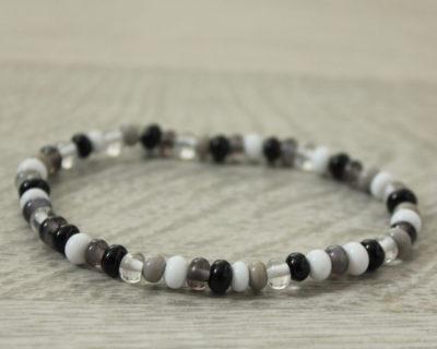 Bracelet fin noir, blanc et gris.